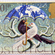 A christmas stamp printed in Grat Britain shows 'World at Peace' (Dove and Blackbird) - Stock fotografie