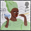 Stock Photo: Stamp printed in Great Britain shos AfricWomeating Rice