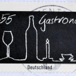GERMANY- CIRCA 2005: stamp printed in Germany dedicated to gastronomy shows glass bottle, candle, cup, circa 2005. - ストック写真