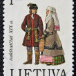 Stock Photo: LITHUANI- CIRC1995: stamp printed in Lithuanishows couple with typical dresses XIX century, circ1995