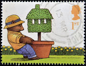 UNITED KINGDOM - CIRCA 2002: A stamp printed in Great Britain shows Bear pulling Potted Topiary Tree (Moving Home), circa 2002 — Stock Photo