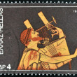 GREECE - CIRCA 1975: A stamp printed in Greece dedicated to the traditional musical instruments shows an ancient guitar player, circa 1975.  — Stock Photo