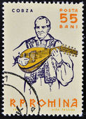 ROMANIA - CIRCA 1961: A stamp printed in Romania shows portrait of traditional musician playing on cobza, folk instrument of the lute family, Circa 1961 — Stock Photo