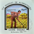Foto Stock: GUINEA-BISSAU - CIRC1983: stamp printed in Republic of Guinea-Bissau commemorative world food day, showing farmer plowing land, circ1983.