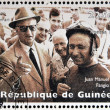 Royalty-Free Stock Photo: GUINEA - CIRCA 1998: Stamp printed in Guinea dedicated to anniversary of Enzo Ferrari, shows Enzo Ferrari and Jose Manuel Fangio, circa 1998