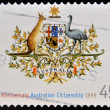 Stock Photo: AUSTRALI- CIRC1999: stamp printed in Australishows Nationality and Citizenship emblem, circ1999