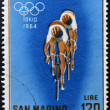 Stock Photo: SAN MARINO - CIRC1964: stamp printed in SMarino shows racing cyclists, 18th Olympic Games, Tokyo, circ1964
