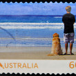 AUSTRALIA - CIRCA 2011: Stamp printed in australia dedicated to living australian, shows young man with his dog watching the sea, circa 2011 — Stock Photo