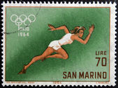 SAN MARINO - CIRCA 1964: A stamp printed in San Marino shows athlete running, 18th Olympic Games, Tokyo, circa 1964 — Stock Photo