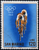 SAN MARINO - CIRCA 1964: A stamp printed in San Marino shows racing cyclists, 18th Olympic Games, Tokyo, circa 1964 — Stock fotografie
