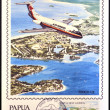 Stockfoto: PAPUNEW GUINE- CIRC1987: stamp printed in Papushows Fokker F28 in flight over of Madang township in Madang Province, circ1987