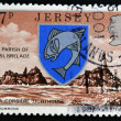 Stock Photo: JERSEY - CIRC1976: stamp printed in Jersey shows Arms of St. Brelade and LCorbiere Lighthouse, circ1976