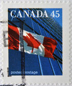 CANADA - CIRCA 1995: A stamp printed in Canada shows image of a the Canadian flag and a modern building, circa 1995 — Stock Photo