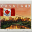 CANADA - CIRCA 2003: A stamp printed in Canada shows flag flying against the backdrop of the city of Edmonton skyline at dawn, circa 2003 — Foto Stock
