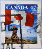 CANADA - CIRCA 2000: A stamp printed in Canada shows the flag fluttering over an inukshuk, circa 2000 — Stock Photo