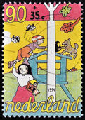 HOLLAND - CIRCA 1994: A stamp printed in The Netherlands dedicated to Child Welfare shows mother holding a child playing, circa 1994 — Stock Photo