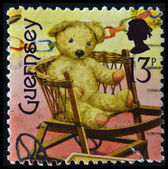 GUERNSEY - CIRCA 1994: A stamp printed in Guernsey dedicated to bygone toys shows teddy bear on a chair, circa 1994 — Stock Photo