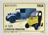 ITALY - CIRCA 2013: Stamp printed in Italy shows an old post car and a contemporary hybrid driven vehicle, circa 2013 — Stock Photo