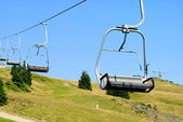 Mountain chair lift with two places for — Stock Photo
