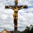 Stock Photo: Golden crucified Christ, dramatic cloudy sky