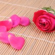 Rose and petals on a bamboo place mat — Stock Photo