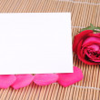 Stock Photo: Rose and petals on bamboo place mat