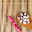 Purple beans over a spoon on a bamboo placemat — Stock Photo