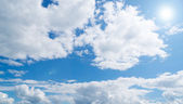Blue sky and fluffy clouds with sun — Stock Photo