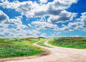 Estrada de terra e as nuvens — Foto Stock