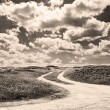 Dirt road and clouds in sepia tone — Foto Stock