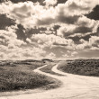 Zdjęcie stockowe: Dirt road and clouds in sepitone