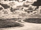 Estrada de terra e nuvens em tom sépia — Foto Stock