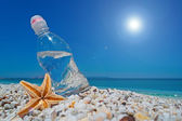 Bottle, sea star and sun — Stock Photo