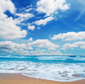 Frothy shore and scenic clouds — Stock Photo