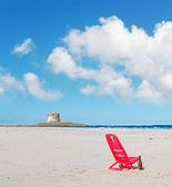 Chair under clouds in La Pelosa — Stock Photo