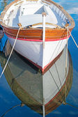 Wooden boat reflection — Stock Photo