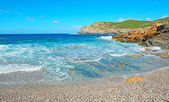 Blue water and pebbles in Argentiera — Stock Photo