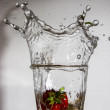 Strawberry falls with a splash in a glass with water — Stock Photo #48258587