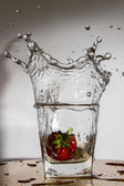 Strawberry falls with a splash in a glass with water — Foto Stock