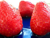 The berries of strawberries on blue saucer — Stock Photo