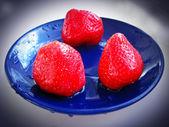 Drie rijpe aardbeien op de blauwe plaat — Stockfoto