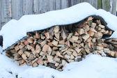 Lenha combinado em heaps sob a neve — Fotografia Stock