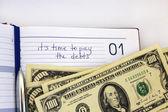 Escrevendo em um caderno sobre uma dívida — Fotografia Stock