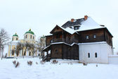 The wooden house and beautiful church in winter — Stock Photo