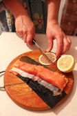 Hand cuts slices of a red fish and lemon — Stockfoto