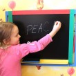 Girl writes on blackboard word the peace - Stok fotoğraf