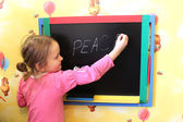Girl writes on blackboard word the peace — Stock Photo
