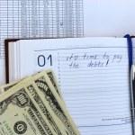 psaní v poznámkovém bloku o dluhu — Stock fotografie