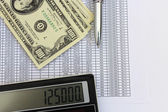 Dollar banknotes, calculator and pen — Stockfoto