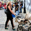 Stock Photo: Mother with perambulator walking along street
